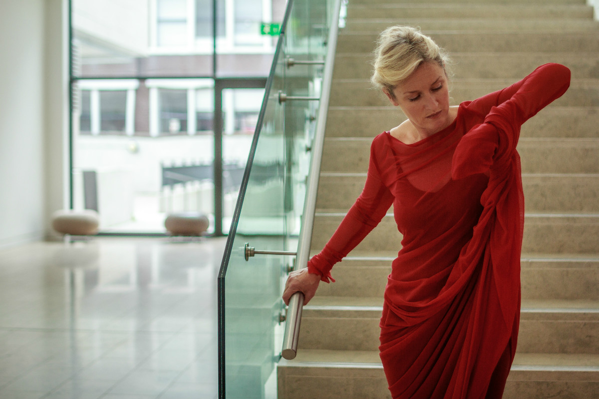 Amanda in red dress on staircase